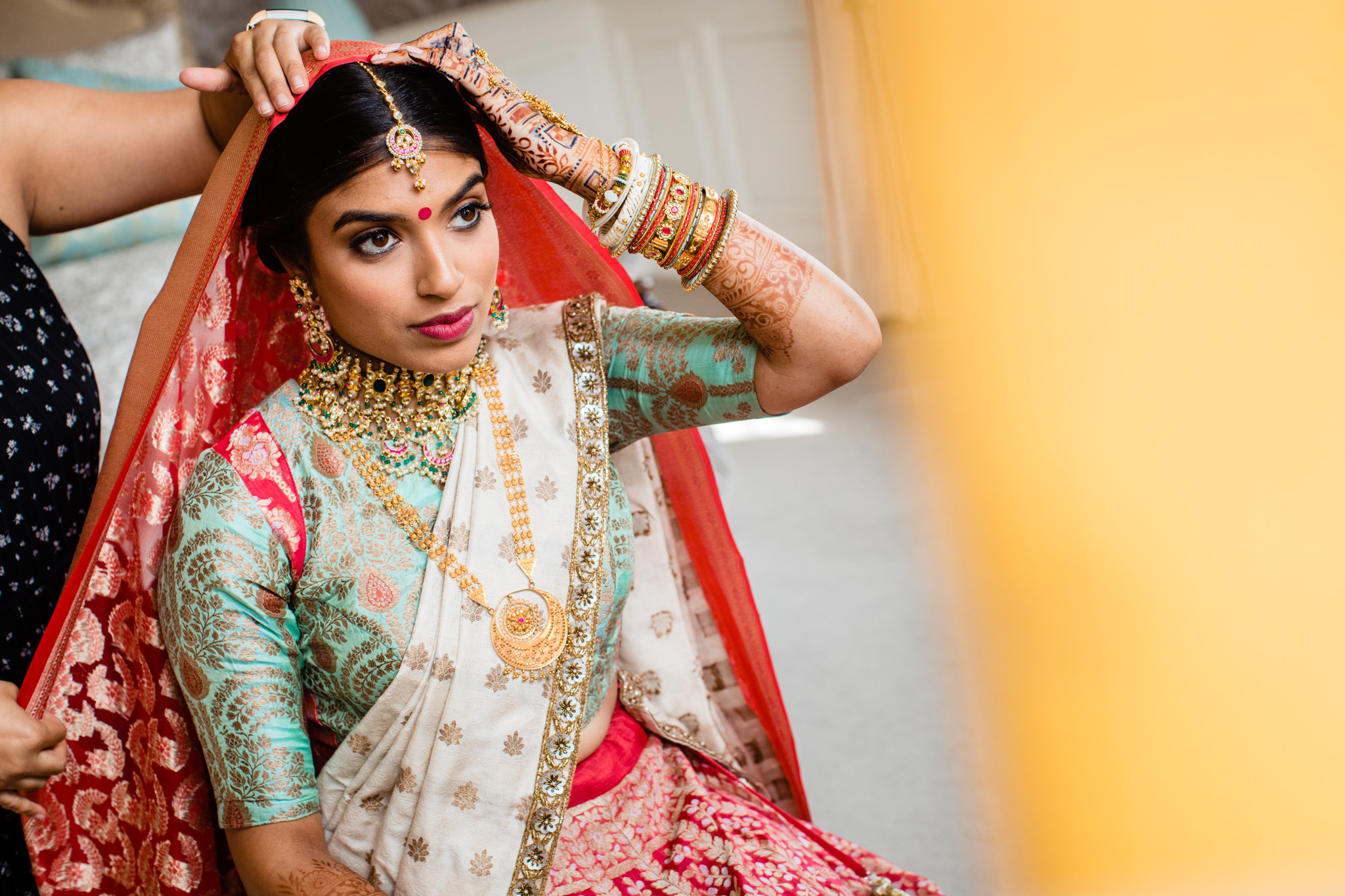 Sikh bride during getting ready in bridal suite looking into the mirror