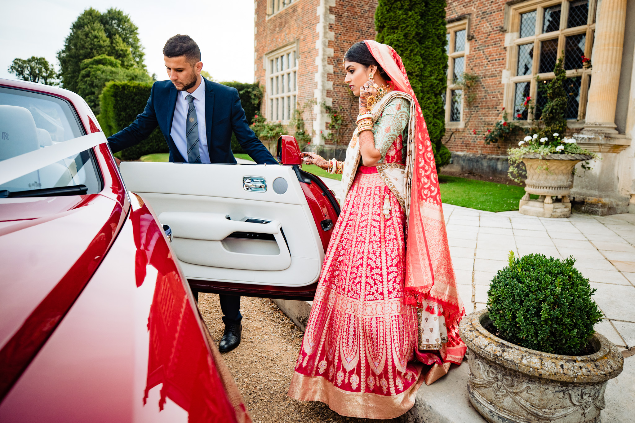 Sikh bride getting into the car at North Mymms Park wedding venue during Sikh wedding