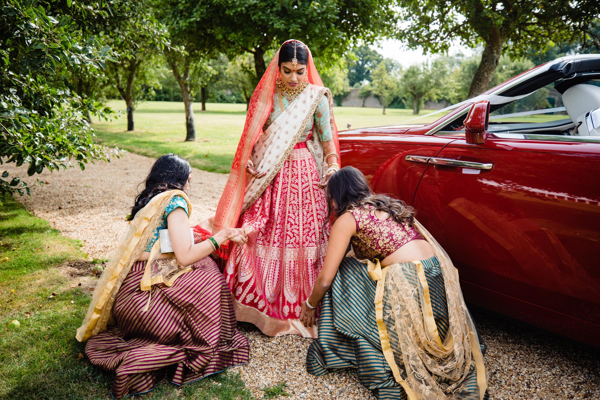 Bridesmaids adjusting the dress of Sikh bride during Sikh wedding