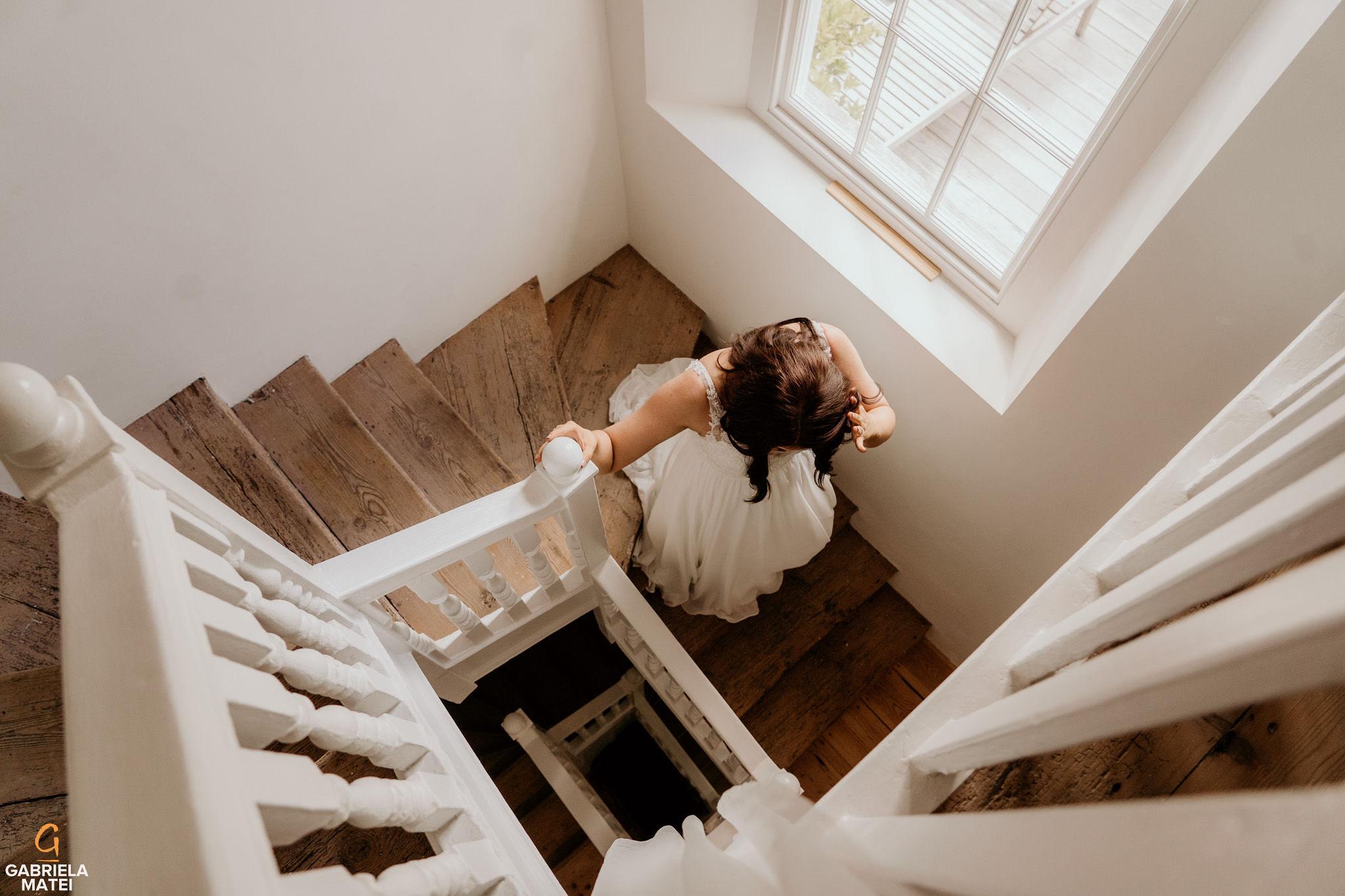 bride walking down indoor staircase at South Stoke Barn wedding venue in Arundel