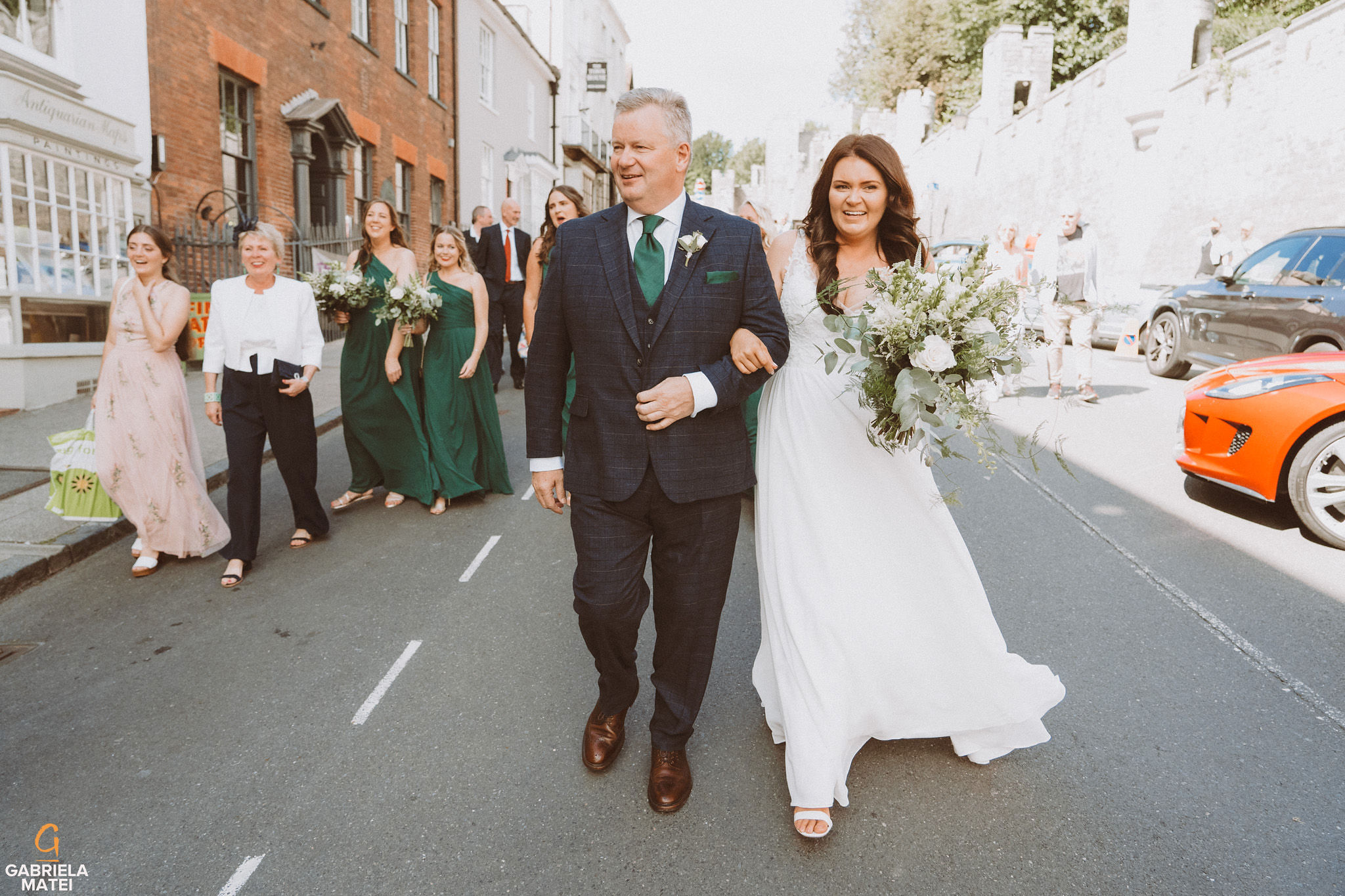 Bride and father of the bride walking down the High Street in Arundel during wedding at at South Stoke Barn wedding venue in Arundel