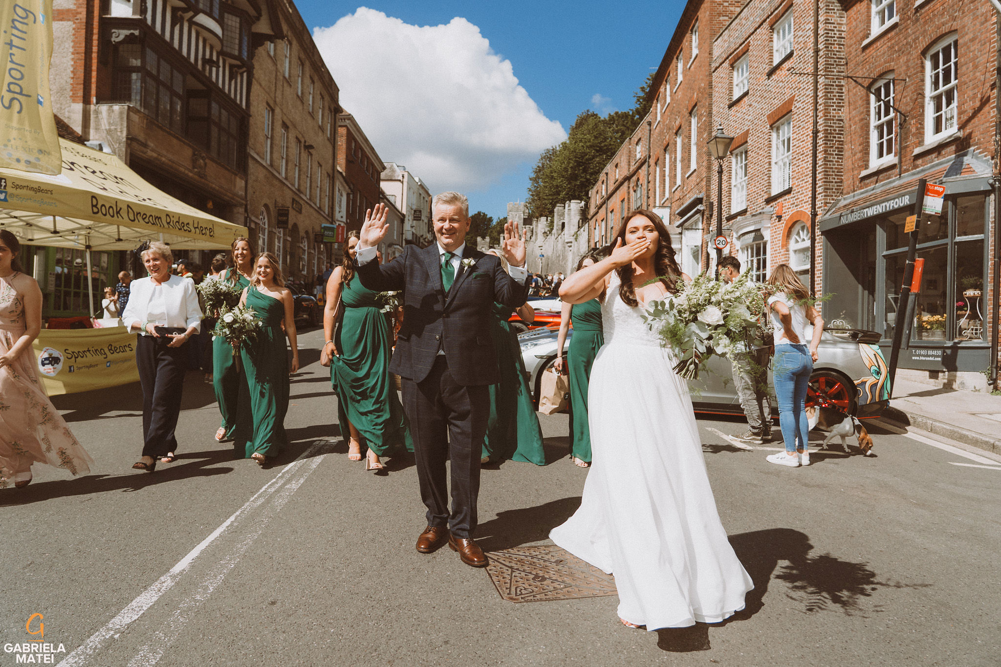 Bride and father of the bride waiving at people whislt they walk on High Street in Arundel on wedding day