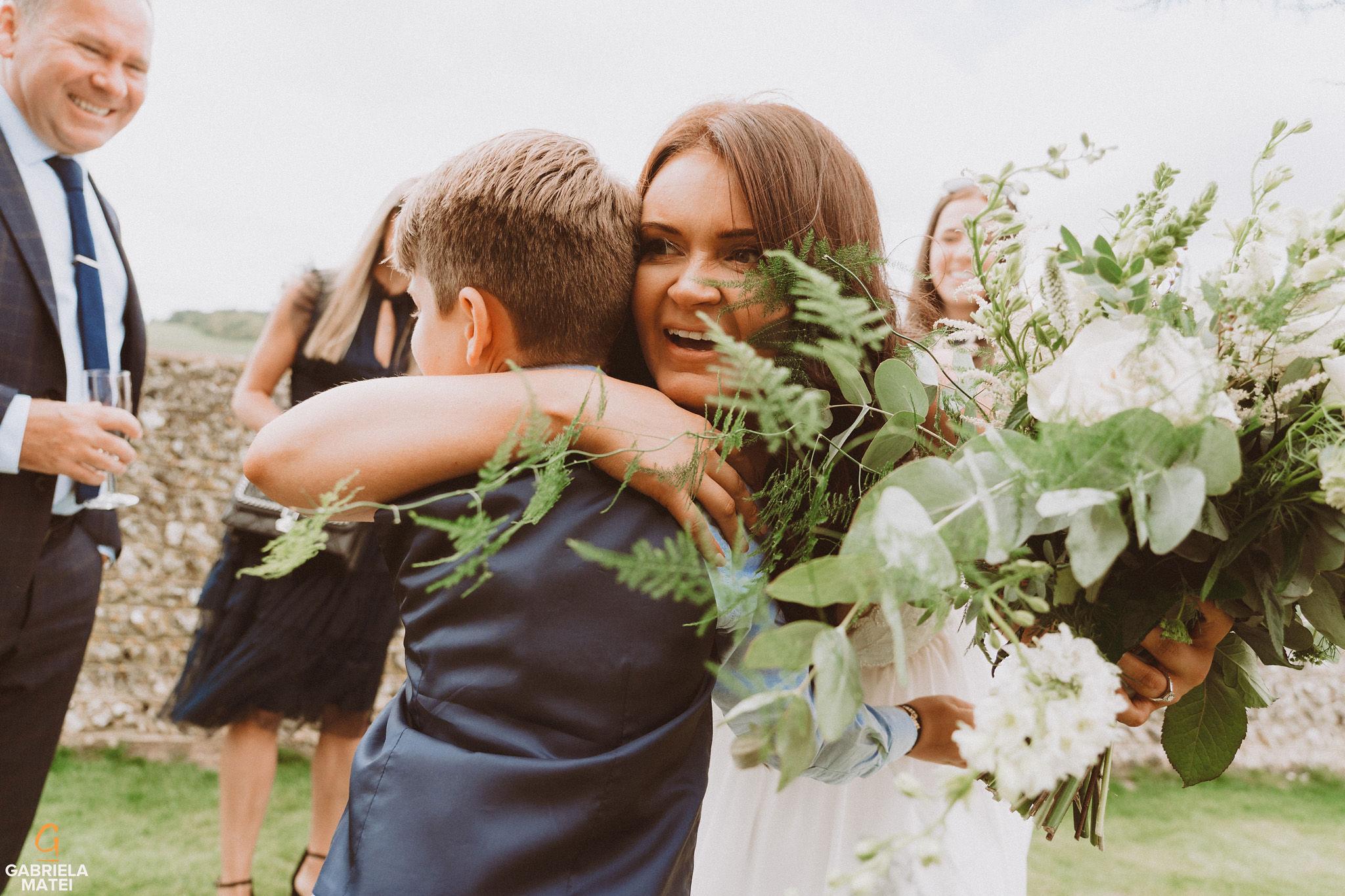 Bride hugging wedding guests at South Stoke Barn wedding venue in Arundel
