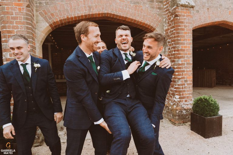 Groom and his groomsmen laughing out loud at South Stoke Barn wedding venue in Arundel by gabriela matei sussex photographer