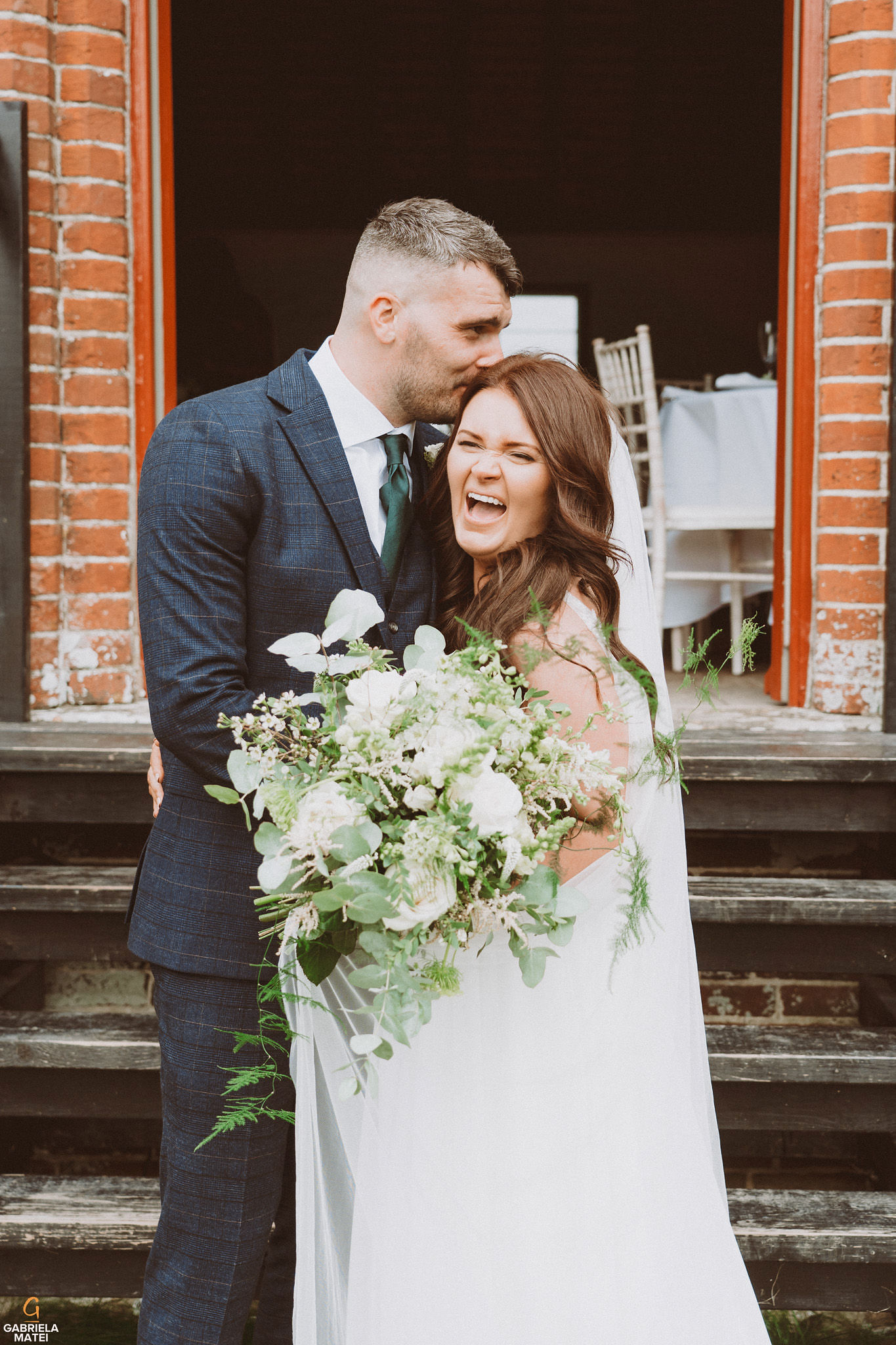 Wedding couple laughing at South Stoke Barn wedding venue in Arundel by gabriela matei sussex photographer