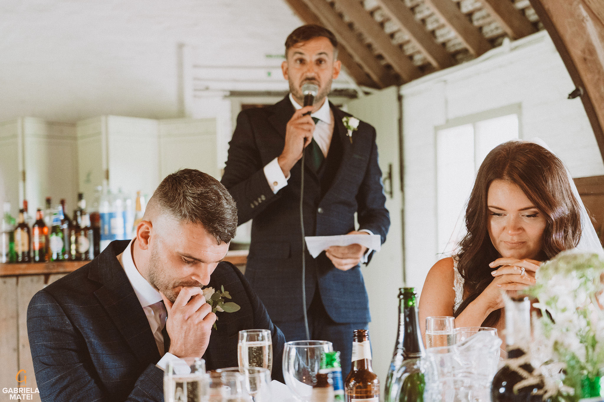 Wedding couple during wedding speeches at South Stoke Barn wedding venue in Arundel by gabriela matei sussex photographer