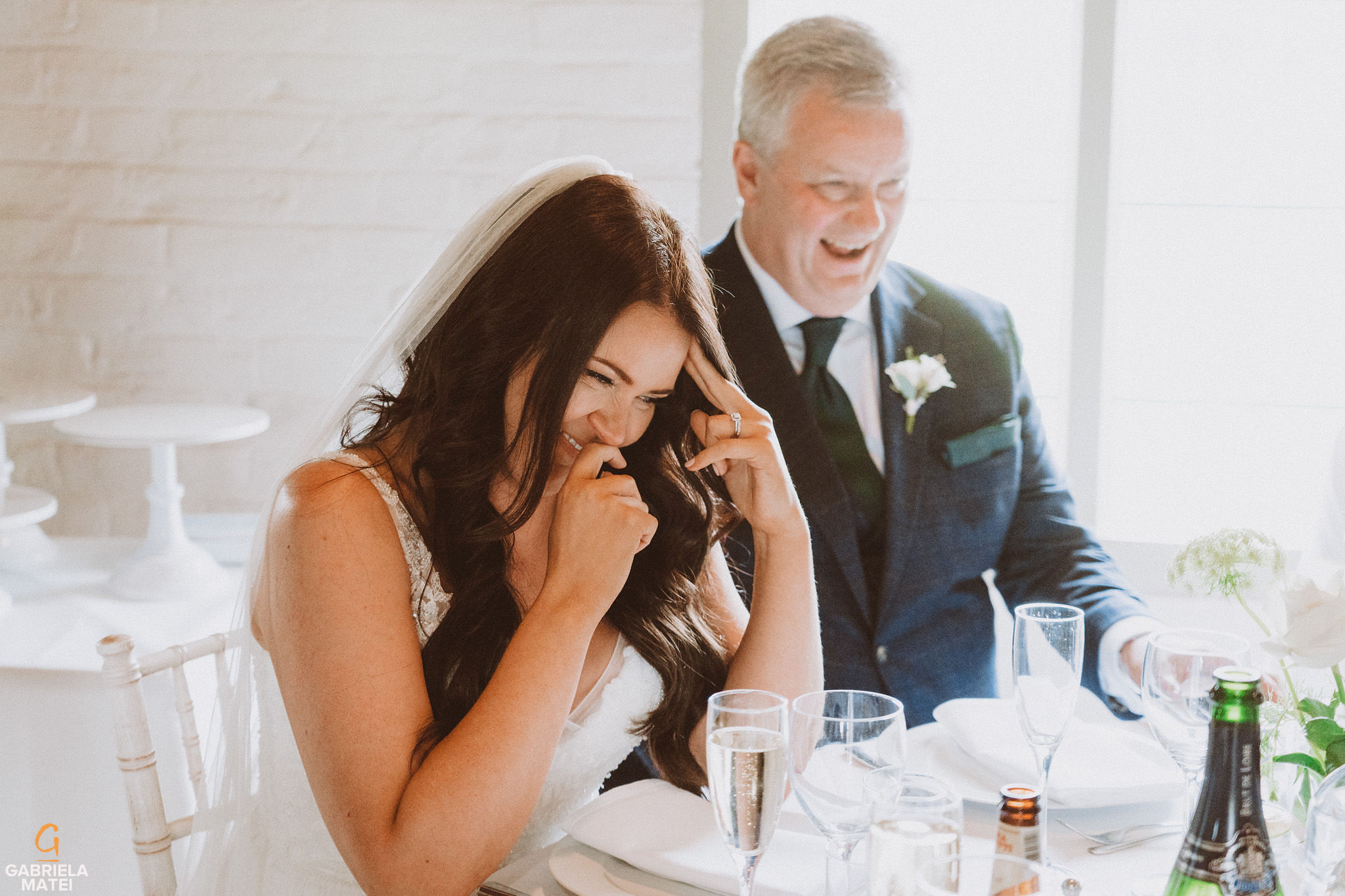 Bride laughing during speeches at South Stoke Barn wedding venue in Arundel by gabriela matei sussex photographer