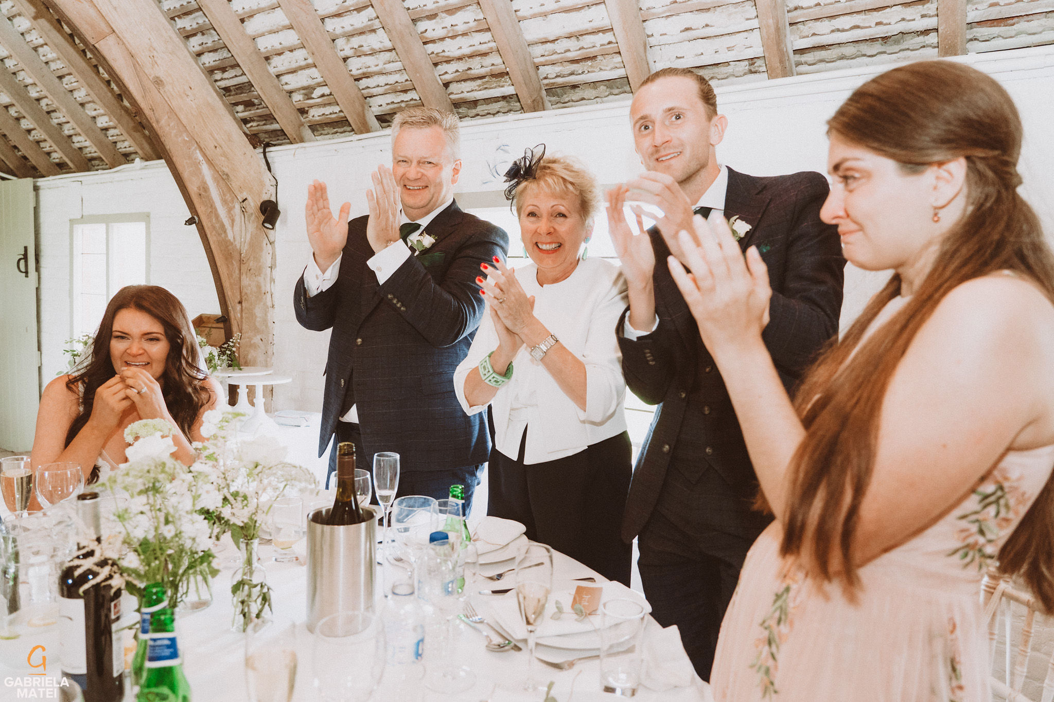 wedding guests clapping of happiness during wedding speeches at South Stoke Barn wedding venue in Arundel by gabriela matei sussex photographer