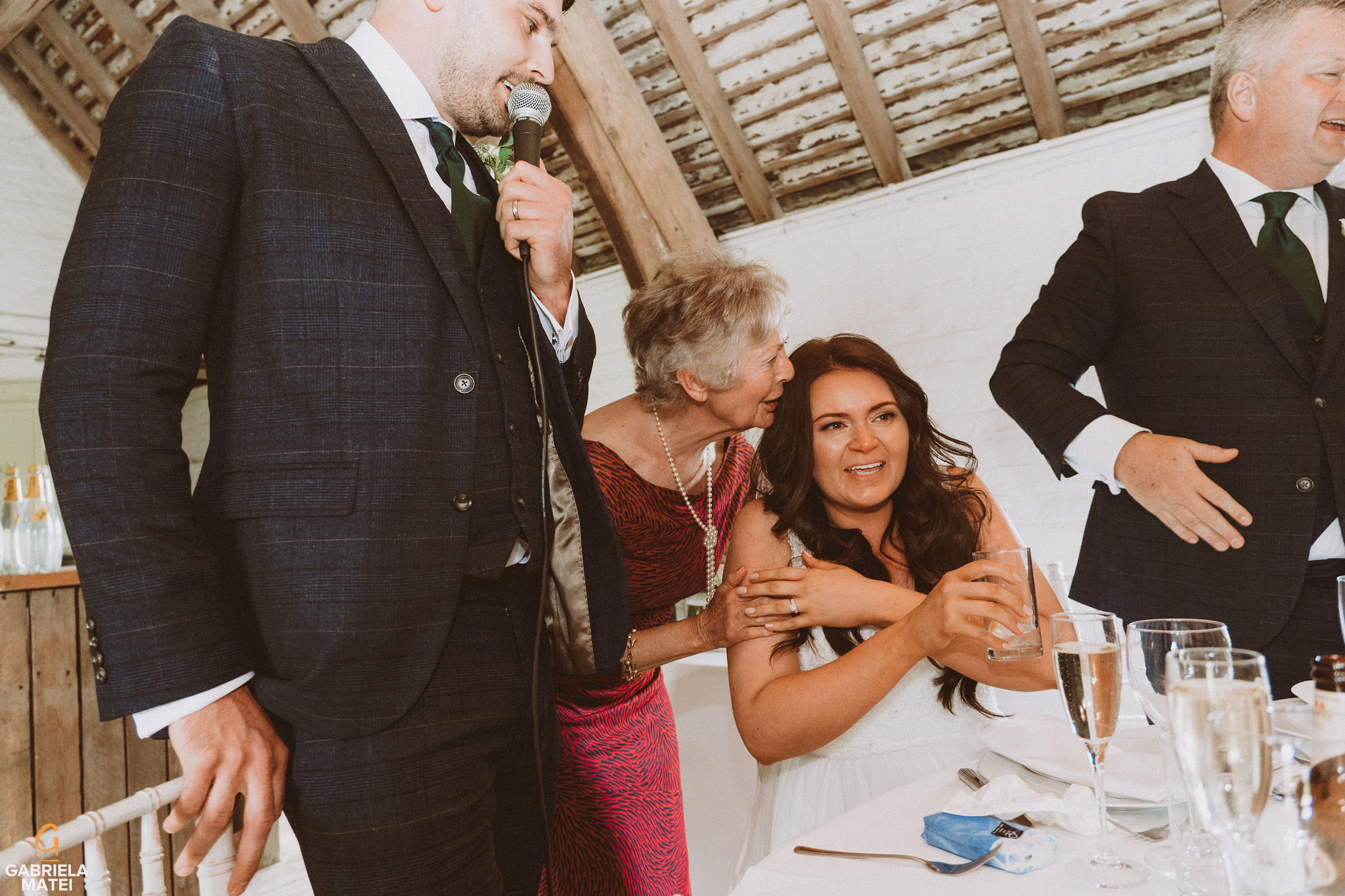Bride crying during wedding speeches at South Stoke Barn wedding venue in Arundel by gabriela matei sussex photographer