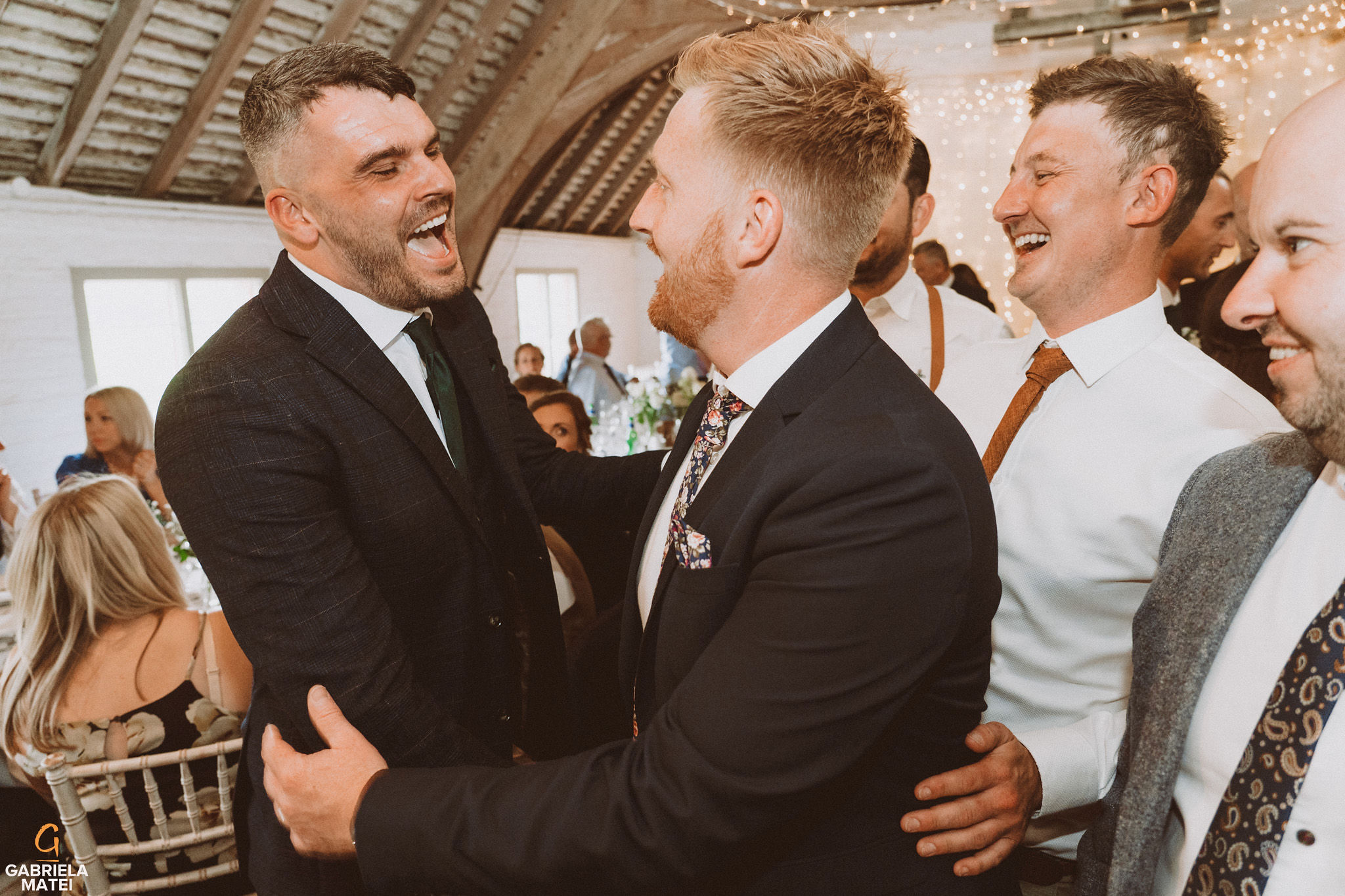 Wedding guests laughing together with the groom at South Stoke Barn wedding venue in Arundel by gabriela matei sussex photographer