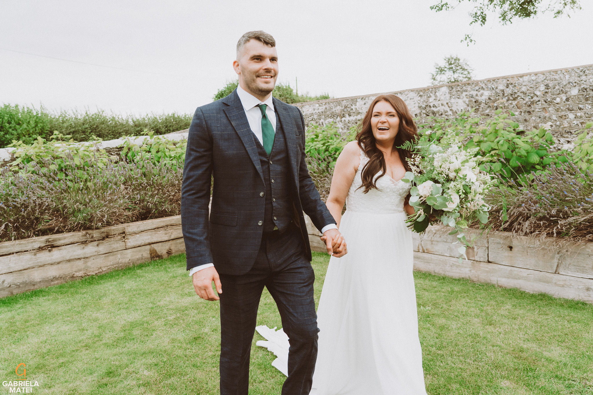 Bride and groom walking hand in hand laughing at South Stoke Barn wedding venue in Arundel by gabriela matei sussex photographer